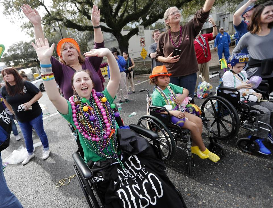 Patients from Children's Hospital of New Orleans waved for beads and trinkets outside the facility during the Krewe of Thoth Mardi Gras parade in New Orleans.