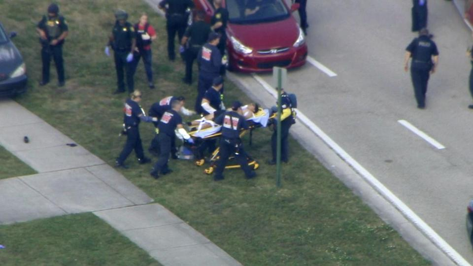 In this frame grab from video provided by WPLG-TV, emergency personnel wheeled an injured person from the Marjory Stoneman Douglas High School in Parkland, Fla., following a shooting there on Wednesday.