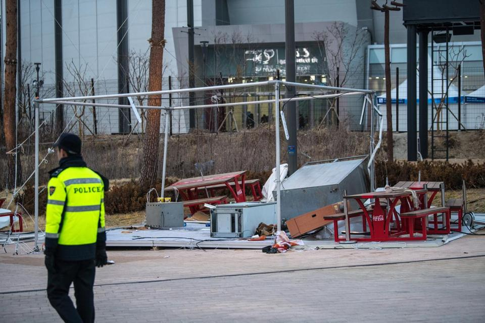GANGNEUNG, SOUTH KOREA - FEBRUARY 14: A police officer guards a temporary structure blown over during high winds in the Gangneung Coastal Cluster during the PyeongChang Winter Olympics on February 14, 2018 in Gangneung, South Korea. Strong winds have caused a number of events to be rescheduled at the PyeongChang Winter Olympics including the biathlon and Alpine skiing competitions. (Photo by Carl Court/Getty Images)