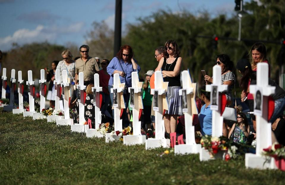 People visited a memorial Sunday for victims of the shooting rampage at the Marjory Stoneman Douglas High School in Parkland, Fla., where 17 people were killed last week.