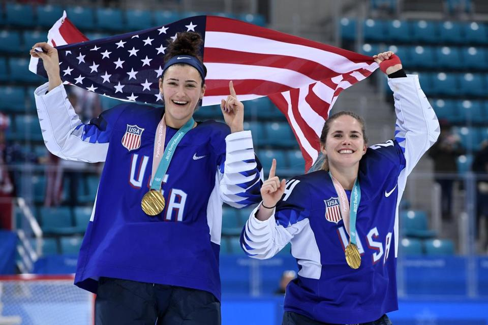 USA's Megan Keller (L) holds the US flag with teammate Danielle Cameranesi after the medal ceremony after winning the women's ice hockey event during the Pyeongchang 2018 Winter Olympic Games at the Gangneung Hockey Centre in Gangneung on February 22, 2018. / AFP PHOTO / JUNG Yeon-JeJUNG YEON-JE/AFP/Getty Images