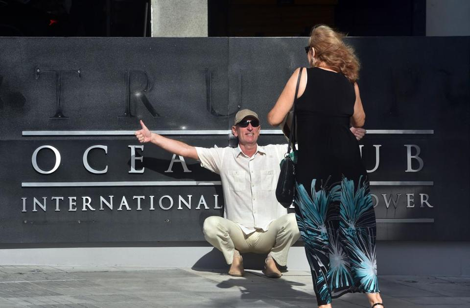 A tourist posed for pictures after a Trump logo was removed from the entrance to the Trump Ocean Club International Hotel and Tower in Panama Cityon Monday.