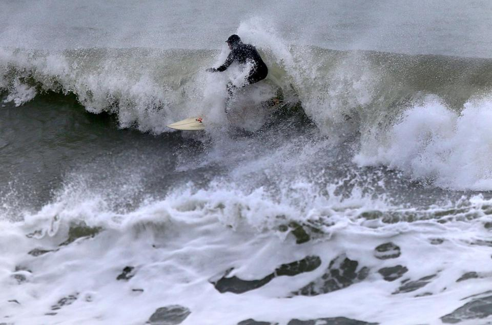 The waves offered a silver lining for this person, who surfed off Devereux Beach in Marshfield on Wednesday.