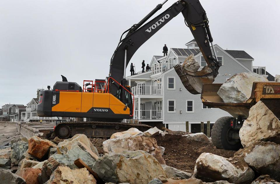 Workers rushed to rebuild a breached seawall Wednesday in the Brant Rock section of Marshfield that was damaged by the last nor'easter.