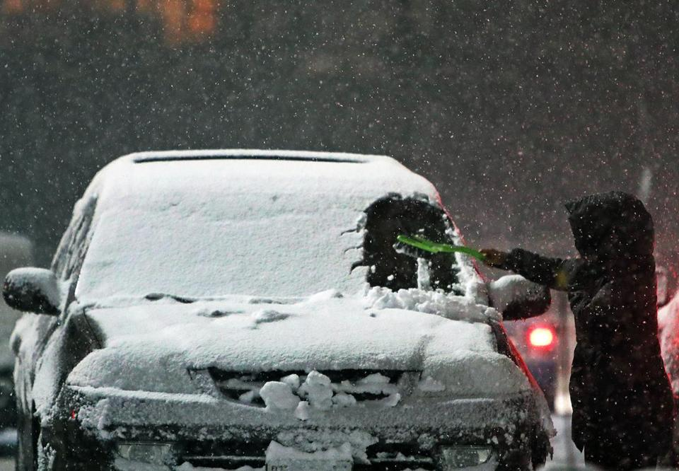 Fitchburg, MA: 3/7/2018: A motorist cleans snow off of their car in the parking lot of the Central Plaza near downtown Fitchburg as the storm intensifies. Another winter storm is predicted to hit the area this afternoon and tonight. (Jim Davis/Globe Staff)