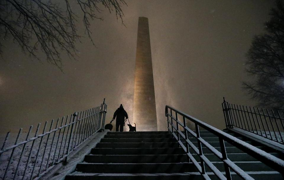 Rudy Hersh took his dogs for their nightly walk as snow swirled around the Bunker Hill Monument during Wednesday's snowstorm.
