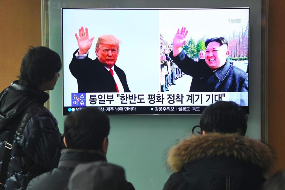People watched a television news report showing pictures of President Trump and North Korean leader Kim Jong Un at a railway station in Seoul on Friday.