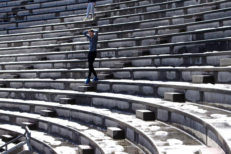 A man climbed steps at Harvard Stadium in Boston on Sunday, with the seats still holding snow from the last storm.