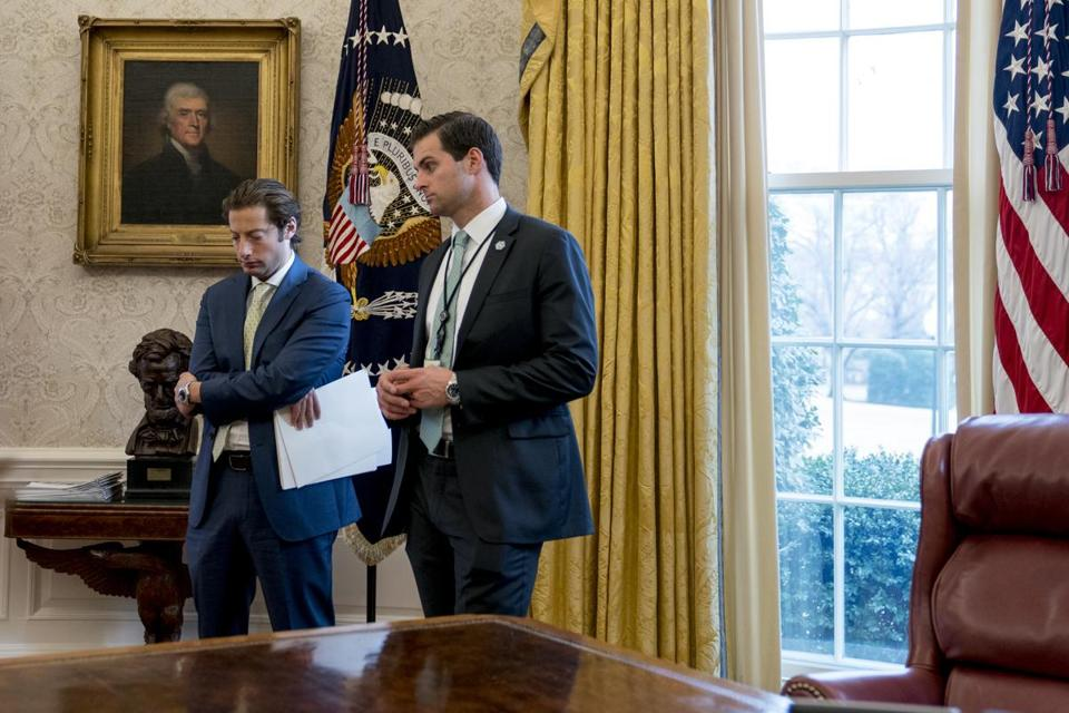 White House aide John McEntee (right) and Treasury Secretary Steve Mnuchin's Chief of Staff Eli Miller (left) stood in the Oval Office as President Donald Trump spoke at a tax reform meeting in January.
