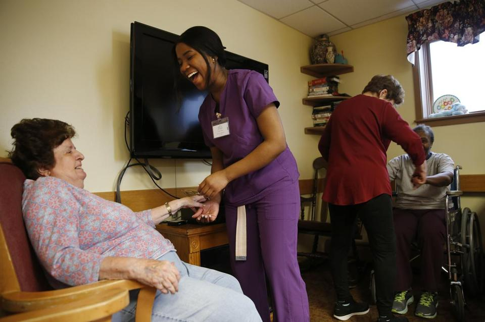 Lynn, MA -- 3/29/2018 - Shaneil Nelson, (C) a senior at Lynn Tech and a registered CNA dances with a resident as she works at Phillips Manor Nursing Home in Lynn. (Jessica Rinaldi/Globe Staff) Topic: 08noscholarship Reporter: