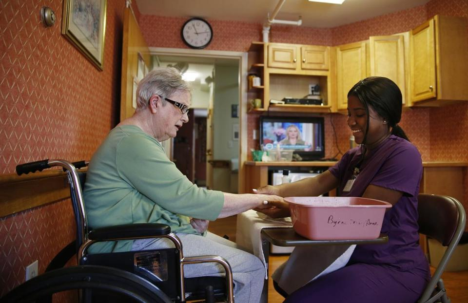 Lynn, MA -- 3/29/2018 - Shaneil Nelson, a senior at Lynn Tech and a registered CNA paints Maryanne Byrne's nails at Phillips Manor Nursing Home in Lynn. (Jessica Rinaldi/Globe Staff) Topic: 08noscholarship Reporter: