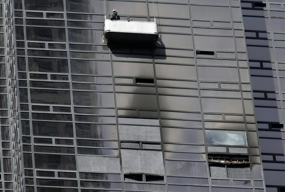 People work above the site of a fatal fire on Trump Tower in New York, Monday, April 9, 2018. A raging fire that tore through a 50th-floor apartment at Trump Tower on Saturday killed a man inside and sent flames and thick, black smoke pouring from windows of the president's namesake skyscraper. (AP Photo/Seth Wenig)