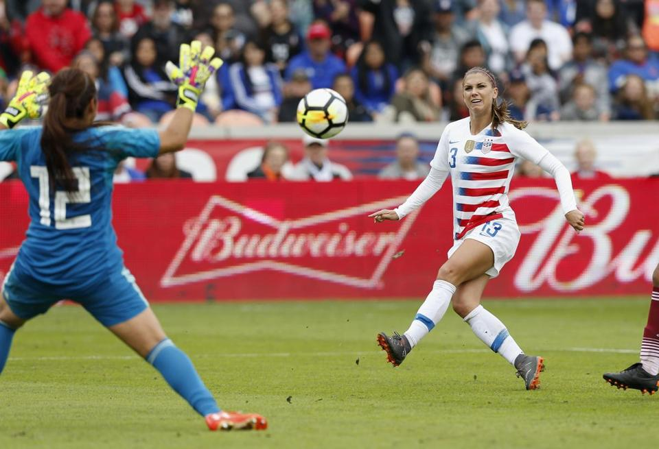 HOUSTON, TX - APRIL 08: Alex Morgan #13 of United States shoots the ball defended by Cecilia Santiago #12 of Mexico in the second half at BBVA Compass Stadium on April 8, 2018 in Houston, Texas. (Photo by Tim Warner/Getty Images)
