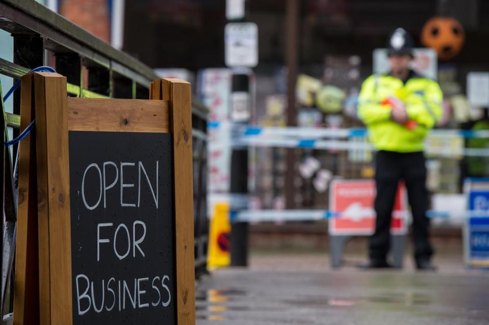 SALISBURY, ENGLAND - APRIL 10: A sign showing local businesses are open next to police officers at a cordon near the scene where former double-agent Sergei Skripal and his daughter, Yulia were discovered after being attacked with a nerve-agent on April 10, 2018 in Salisbury, England. Russian ex-spy Sergei Skripal and his daughter Yulia Skripal were attacked with nerve agent Novichok in Salisbury on March 4, 2018 and have since been under the care of Salisbury District Hospital. Yulia Skripal has now been discharged from the hospital and taken to a secure location while her father remains at the hospital but no longer in a critical condition. (Photo by Chris J Ratcliffe/Getty Images)