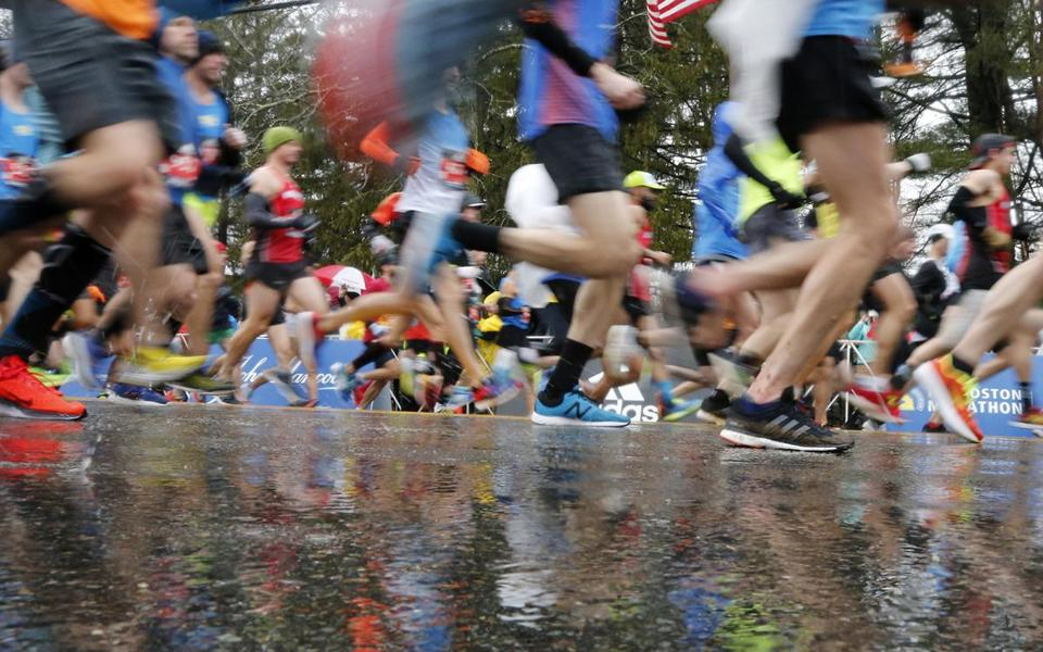MARATHON SLIDER Runners in the first wave break from the start on rain soaked streets during the 122nd running of the Boston Marathon in Hopkinton, Mass., Monday, April 16, 2018. (AP Photo/Mary Schwalm)