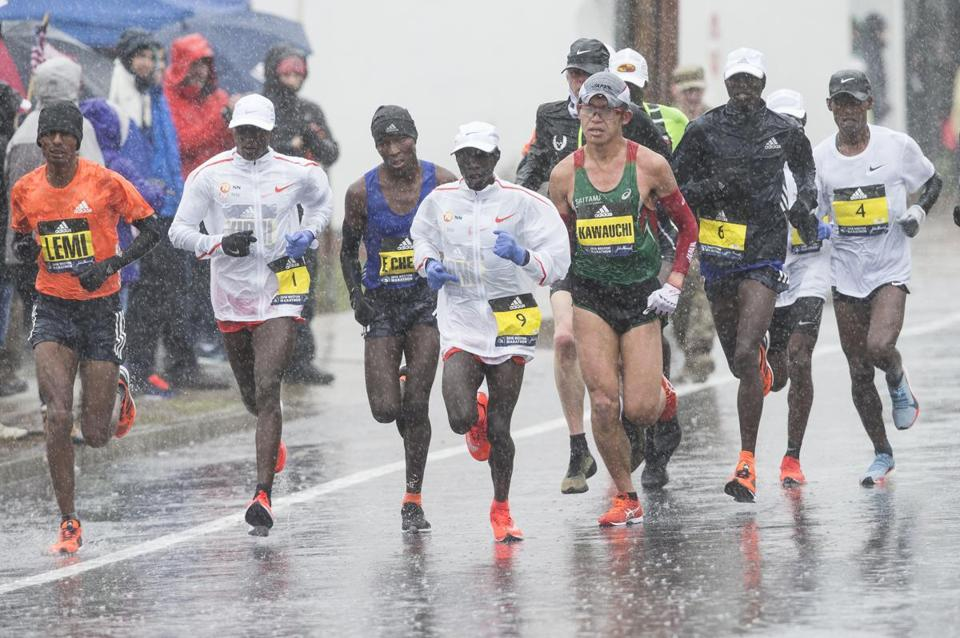 A pack of elite men splashes through Needham on a miserable weather day.