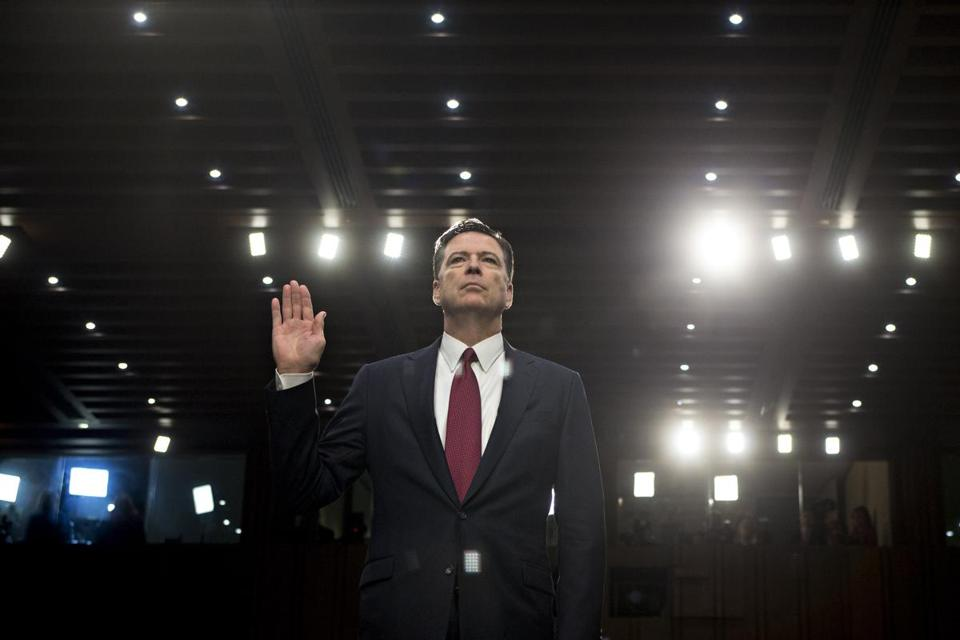 James Comey former director of the FBI swears in to a Senate Intelligence Committee hearing in Washington