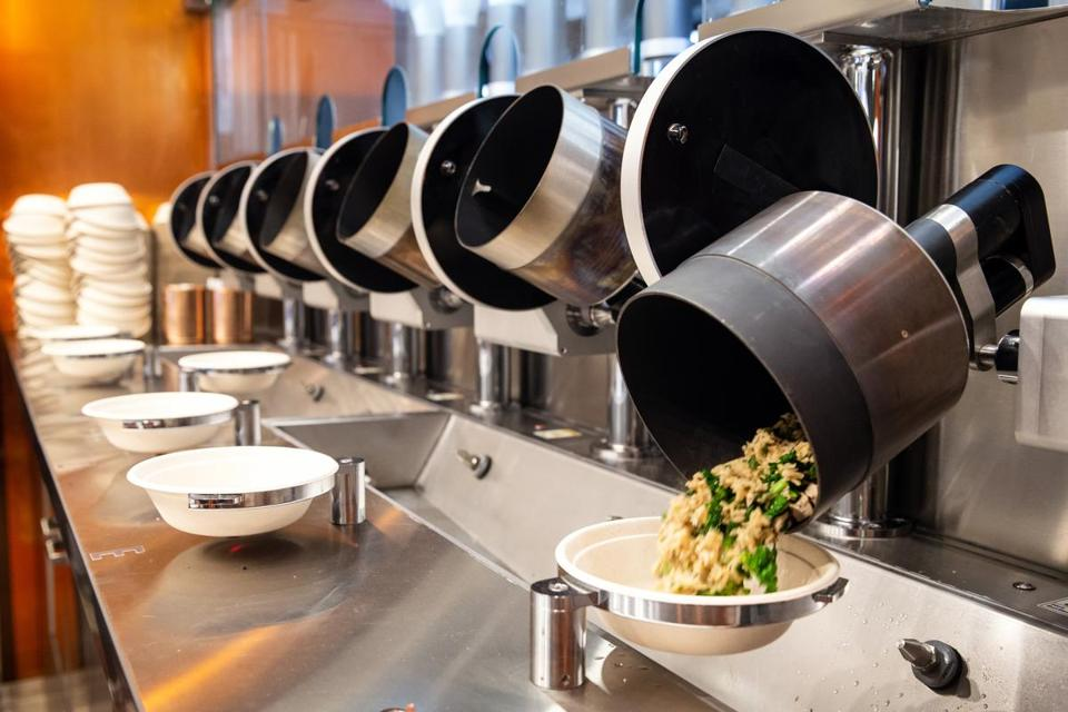 An automated wok dumps finished food into bowl at Spyce in Boston.