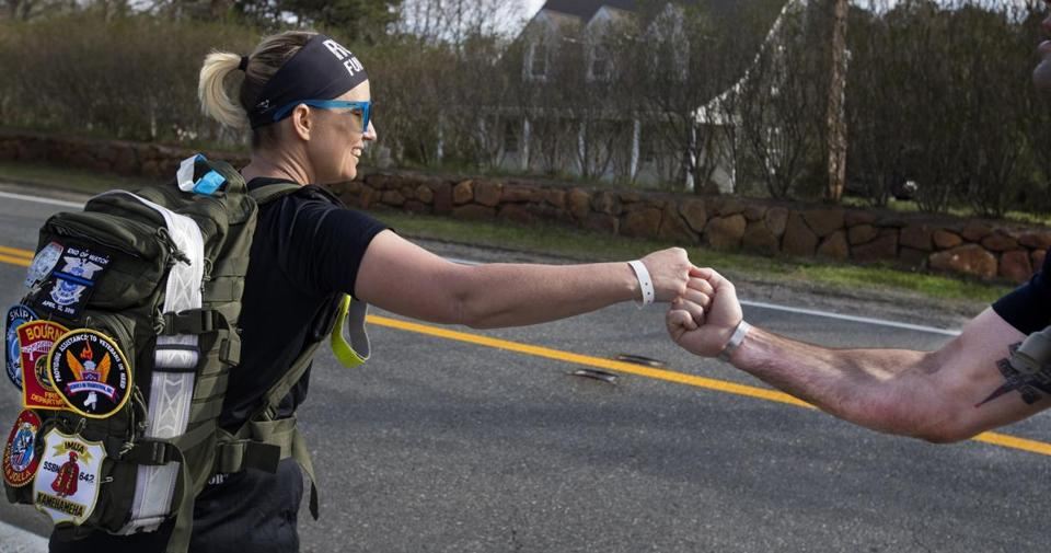 Runner Lindsey Mahoney, toting a 20-pound rucksack, fist-bumps a teammmate.
