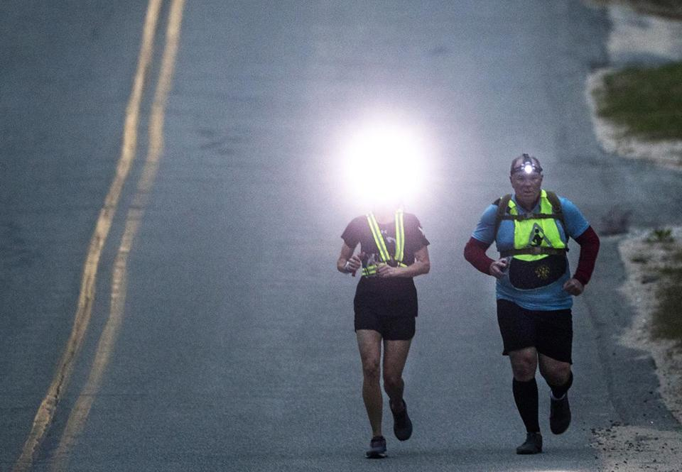 Truro- May 4, 2018- Stan Grossfeld/Globe Staff- Support runner Lindsay Ruthven (left) lights the way for fromTeam Spencer's Mike McGrail on the downhill from Truro. Ruck4HIT organizers allowed two night support runners-Friday night 7pm-7 am Saturday morning for support runners to accompany runners during the hardest few hours of the event..