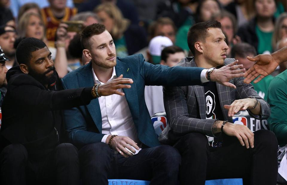 Kyrie Irving (left) and Gordon Hayward (center) joined other boldfacers in the front row for Sunday's game.