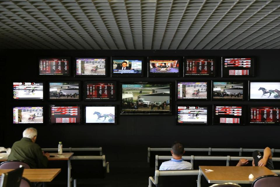 Men watch horse racing on an array of screen at Monmouth Park Racetrack in Oceanport, N.J., Monday, May 14, 2018. The Supreme Court on Monday gave its go-ahead for states to allow gambling on sports across the nation, striking down a federal law that barred betting on football, basketball, baseball and other sports in most states. (AP Photo/Seth Wenig)