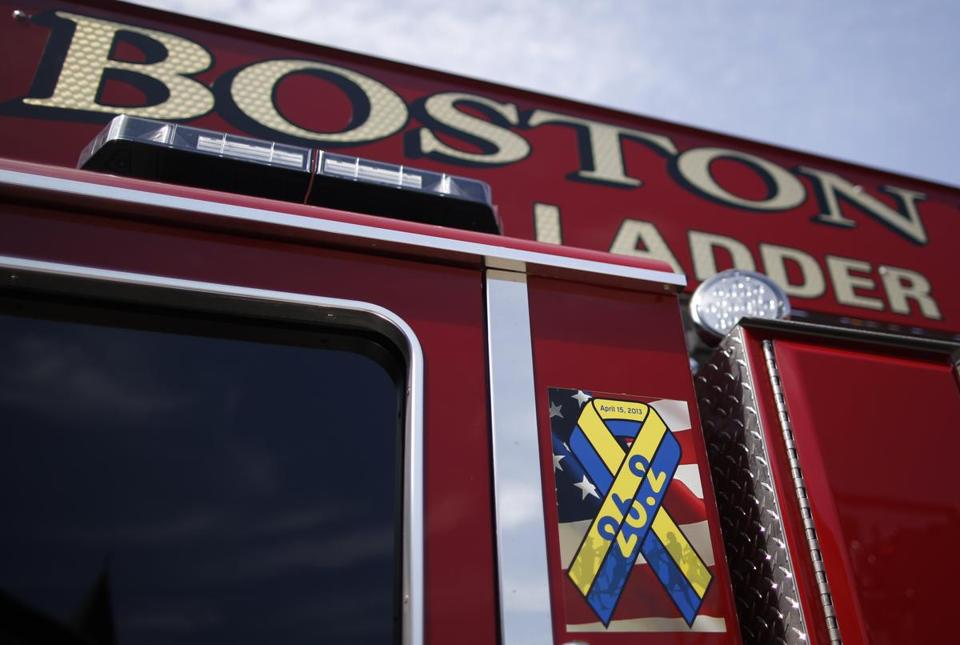 A ribbon honoring the victims of the Boston Marathon bombings is seen on the side of Mattapan Ladder 29 as the new ladder trucks enter Boston Fire Department service in South Boston, Massachusetts August 19, 2013. (Jessica Rinaldi For The Boston Globe)