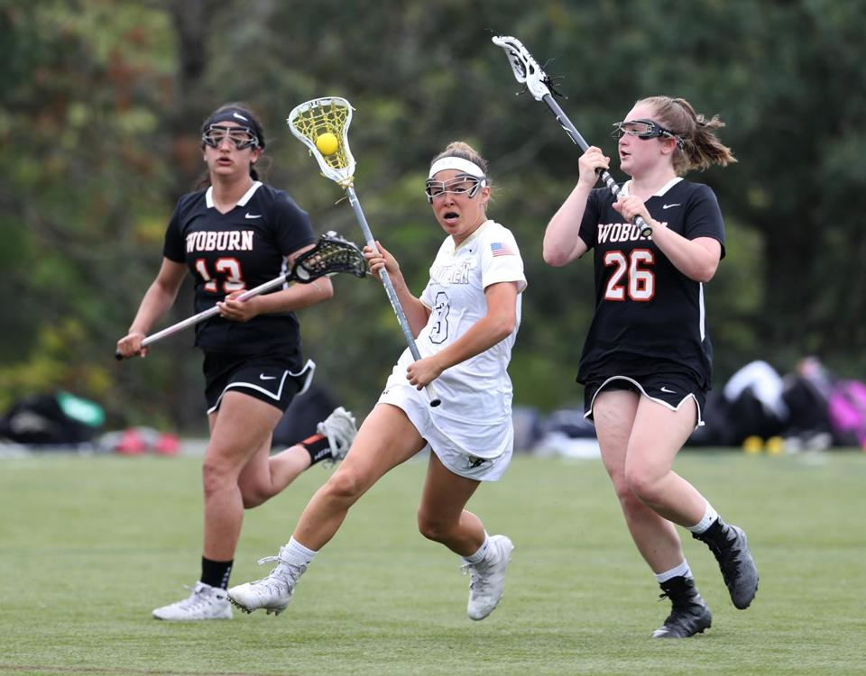 May 15, 2018 -- Lexington , MA - Lexington no. 3. Abby Cheng gets chased by Woburn's no. 13 Georgie Santullo left, and no 26.Emma LaRusso, at Lexington vs. Woburn girls' high school lacrosse. (Joanne Rathe/ Globe Staff)