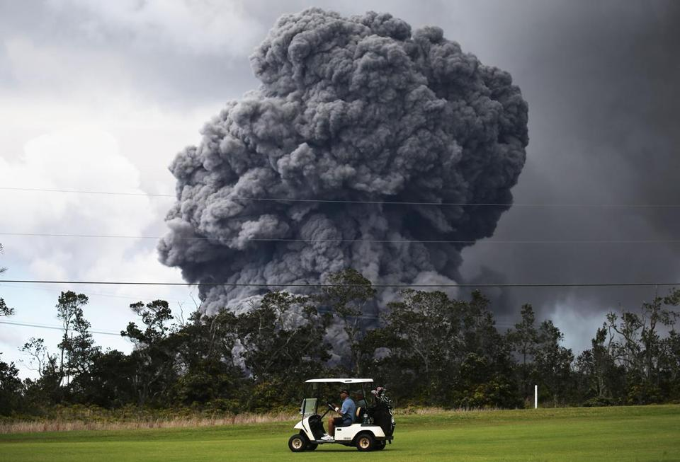 A man drove a cart at a golf course as an ash plume rose in the distance from the Kilauea volcano on Hawaii's Big Island Tuesday.