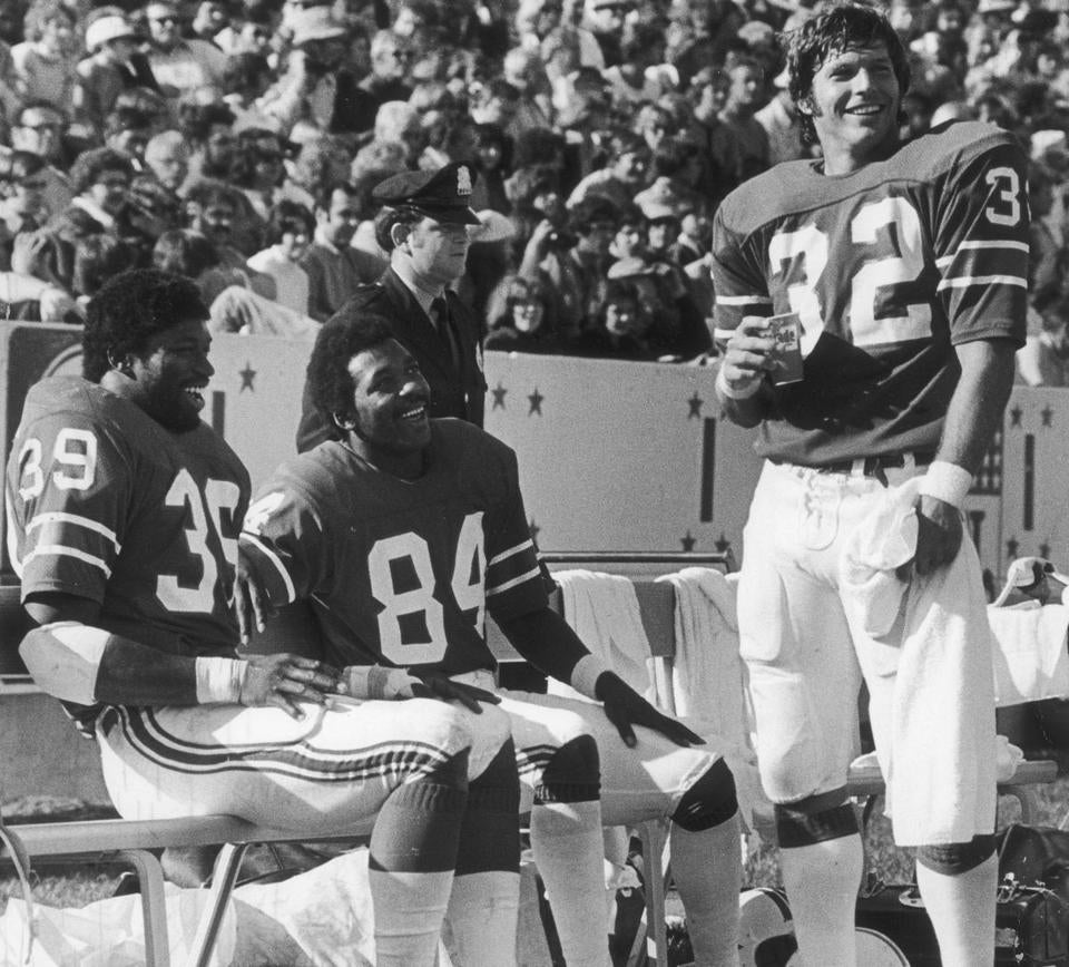 "October 3, 1976 / fromthearchive / Globe staff photo by Frank O'Brien / Fullback Sam Cunningham and wide receiver Darryl Stingley laugh with running back Andy Johnson as they celebrate a Patriot thrashing of the Oakland Raiders 48-17. ""No one has ever done this to one of my teams,"" said Raider coach John Madden after Oakland was pushed all over the field to the delight of a sellout crowd of 61,068. Cunningham rushed for 101 yards and caught passes for 94 more. Stingley caught two touchdown passes and rushed for 48 yards on two reverses."