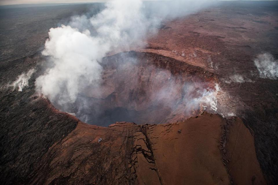 Mandatory Credit: Photo by BRUCE OMORI/PARADISE HELICOPTERS/EPA-EFE/REX/Shutterstock (9678549a) An aerial view shows smoke rising from the Pu'u 'O'o crater on Hawaii's Big Island, 16 May 2017, where the crater's floor collapsed about two weeks ago, covering just about the entire upper flow field with a layer of red ashes and leaving a bottomless pit with no visible lava (issued 17 May 2018). Magma that occupied large underground storage chambers likely headed down the east rift zone to an increasing number of fissure eruptions. Kilauea is the most active volcano on the Hawaii's Big Island and some experts predict the volcanic activity could cause a massive explosion in the coming weeks. Experts predict massive volcano eruption on Hawaii, Pahoa, USA - 14 May 2018