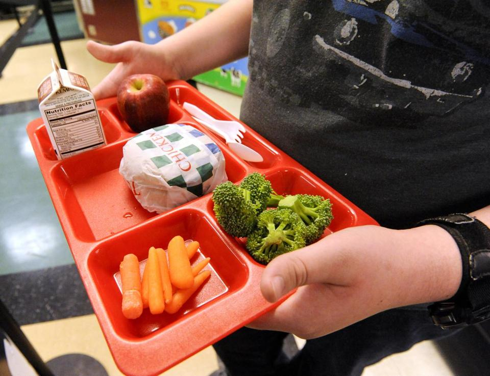 ADVANCE FOR RELEASE MONDAY, MARCH 3, 2014, AND THEREAFTER - In this Feb. 24, 2014 photo, eighth-grader Brett Hein shows the three healthy food items from the fruit and vegetable serving cart during lunch in the cafeteria at Wilson Junior High School in Manitowoc, Wis. Each student is required to take at least one-half cup of fruit or vegetable per the United States Department of Agriculture requirement. (AP Photo/Herald-Times Reporter, Sue Pischke) NO SALES