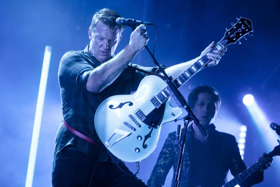 Josh Homme, left, performs with Queens of the Stone Age at Boston Calling Saturday night.