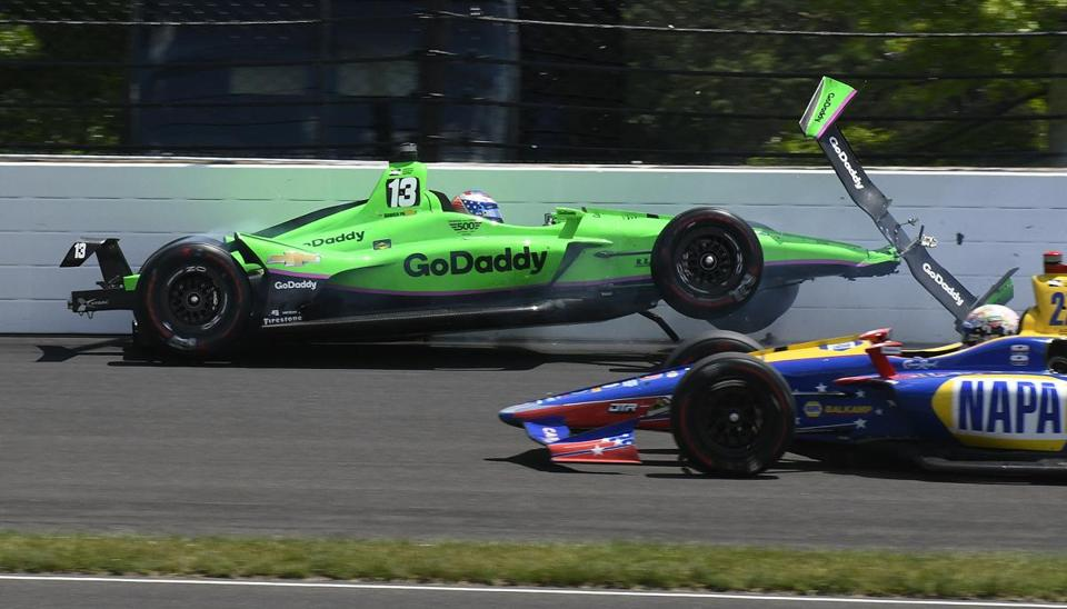 Alexander Rossi drives by Danica Patrick as she hits the wall in the second turn during the running of the Indianapolis 500 auto race at Indianapolis Motor Speedway in Indianapolis Sunday