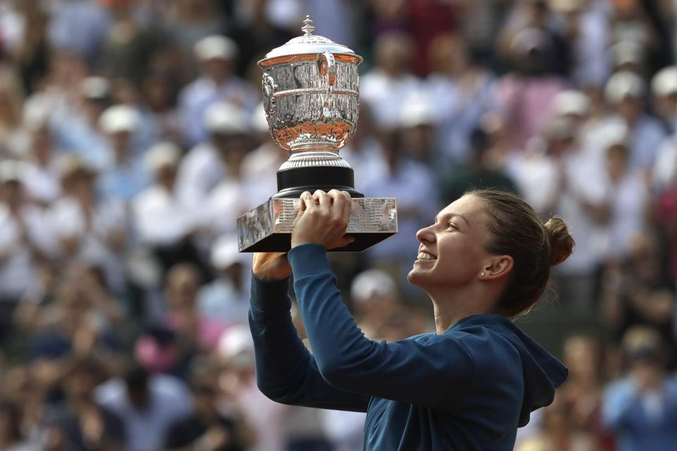 Romania's Simona Halep holds the trophy as she celebrates wining the final match of the French Open tennis tournament against Sloane Stephens of the U.S. in three sets 3-6, 6-4, 6-1, at the Roland Garros stadium in Paris, France, Saturday, June 9, 2018. (AP Photo/Alessandra Tarantino)