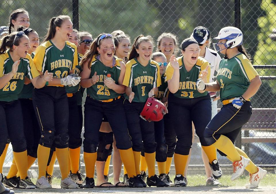 North Reading's Tara Driver, right, is greeted at home by her teammates after hitting a two-run home run during their win over Arlington Catholic in North Reading, Mass., Sunday, June 10, 2018. (Winslow Townson for The Boston Globe)