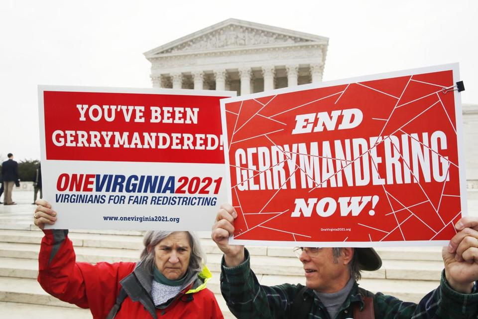 Sara Fitzgerald, left, and Michael Martin, both with the group One Virginia, protest gerrymandering in front of the Supreme Court, Wednesday, March 28, 2018, in Washington where the court will hear arguments on a gerrymandering case. The Supreme Court is taking up its second big partisan redistricting case of the term amid signs the justices could place limits on drawing maps for political gain. (AP Photo/Jacquelyn Martin)