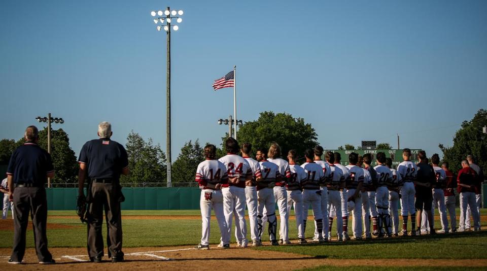 The umpires and Lowell High's baseball team stand and face the American flag as the national anthem streams from the announcer's box before the Red Raiders' win over Newton North in the MIAA Division 1 North quarterfinals Monday.