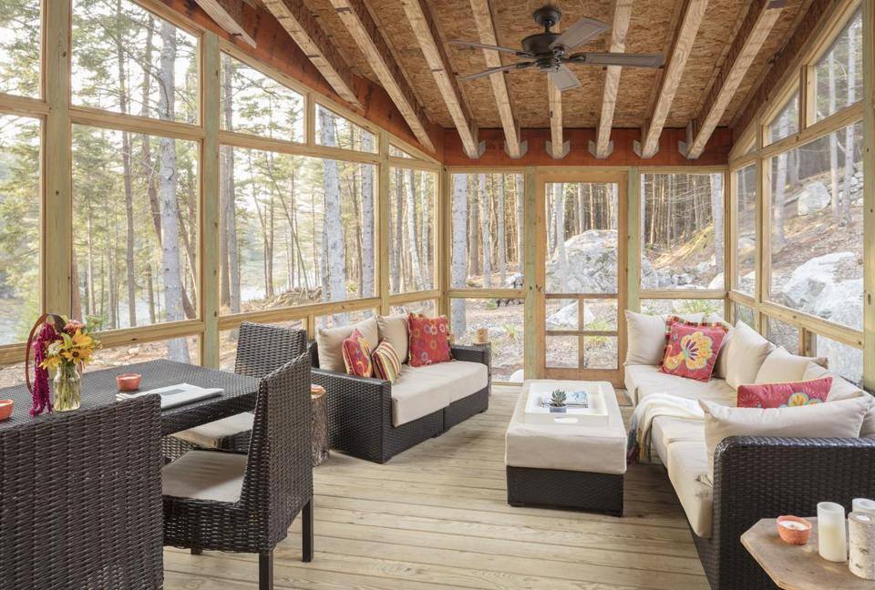 The screened porch was built from low-cost materials, including exterior-grade particleboard for the ceiling. Beyond the door, a large rock outcropping provides a focal point.