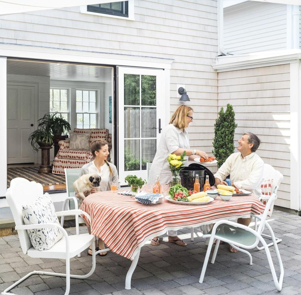 Designer Beth Odence, daughter Charlotte (holding Dexter the pug), and husband Phil enjoy lunch on the patio.