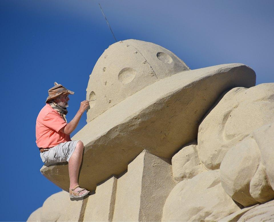 A sculptor is hard at work crafting a UFO out of sand on Hampton Beach.
