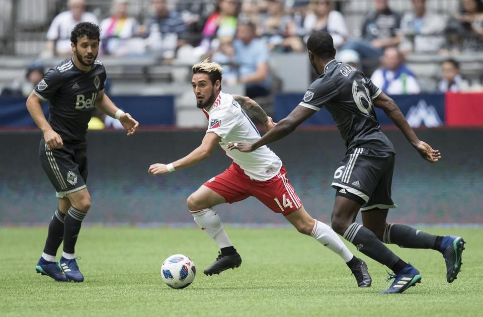 New England Revolution's Diego Fagundez, center, controls the ball while watched by Vancouver Whitecaps' Felipe Martins, left, and Ali Ghazal during the first half of an MLS soccer game in Vancouver, British Columbia, Saturday, May 26, 2018. (Darryl Dyck/The Canadian Press via AP)