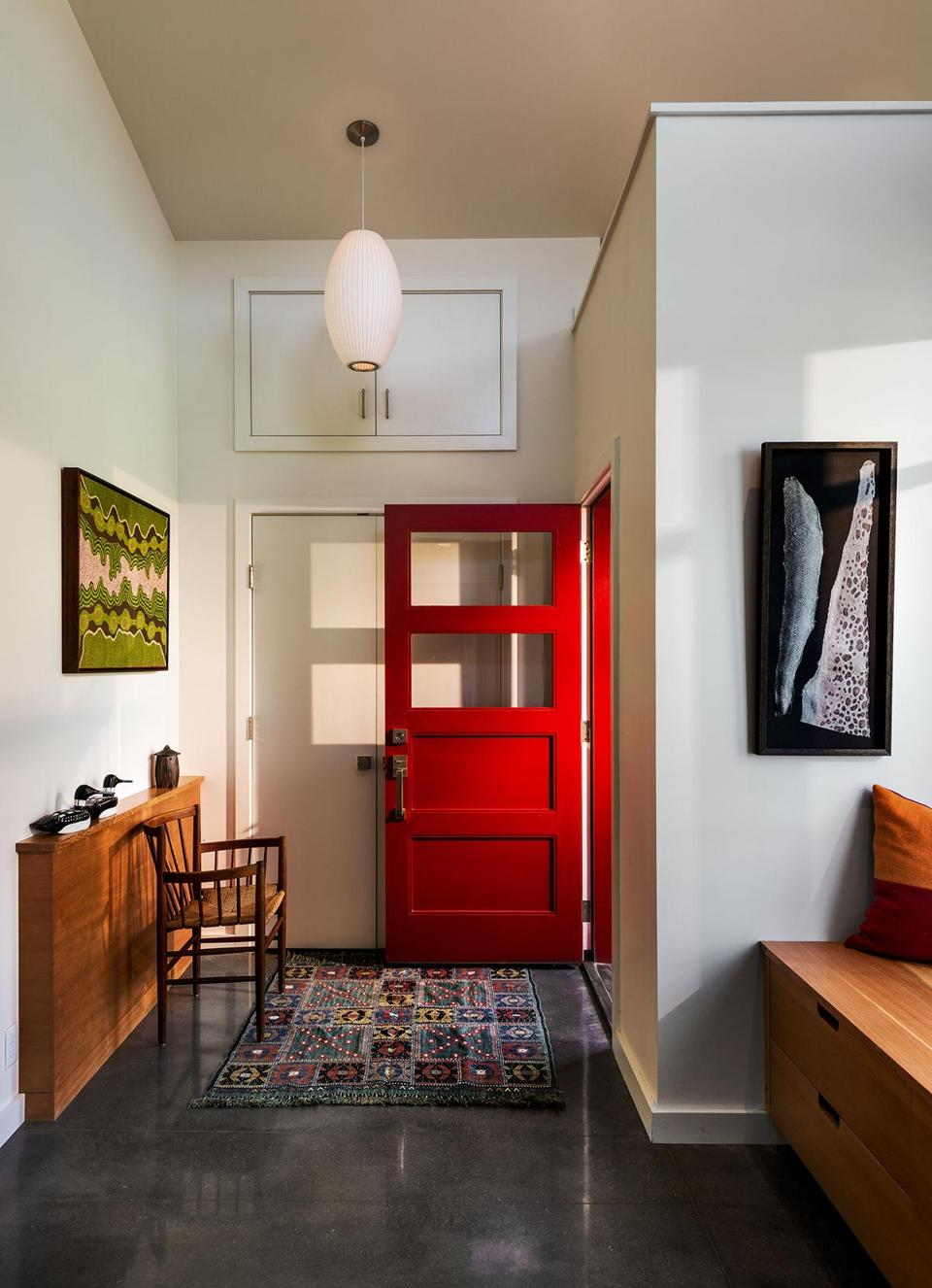 Architect Ira Clark designed the narrow fir ledge in the entry to hold keys and such. A painting by an Aboriginal artist that the homeowners bought in Australia hangs above. Two pieces of fish-skin leather they brought back from Iceland and framed hang by the window seat.