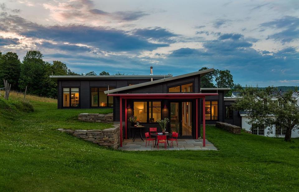 The tubular frame of the pergola is painted bright red to match the Barn Light Electric Company sconces. The 1,700-square-foot addition is connected to the original farmhouse by a passageway at right.