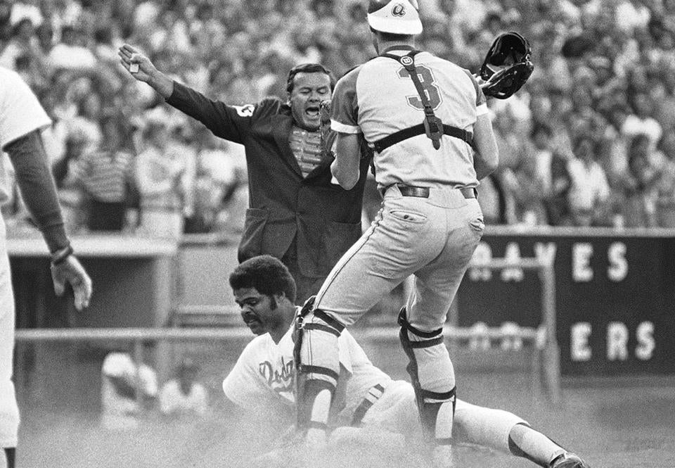Umpire Dutch Rennert is shown in a 1978 game, with Braves catcher Dale Murphy and the Dodgers' Reggie Smith.