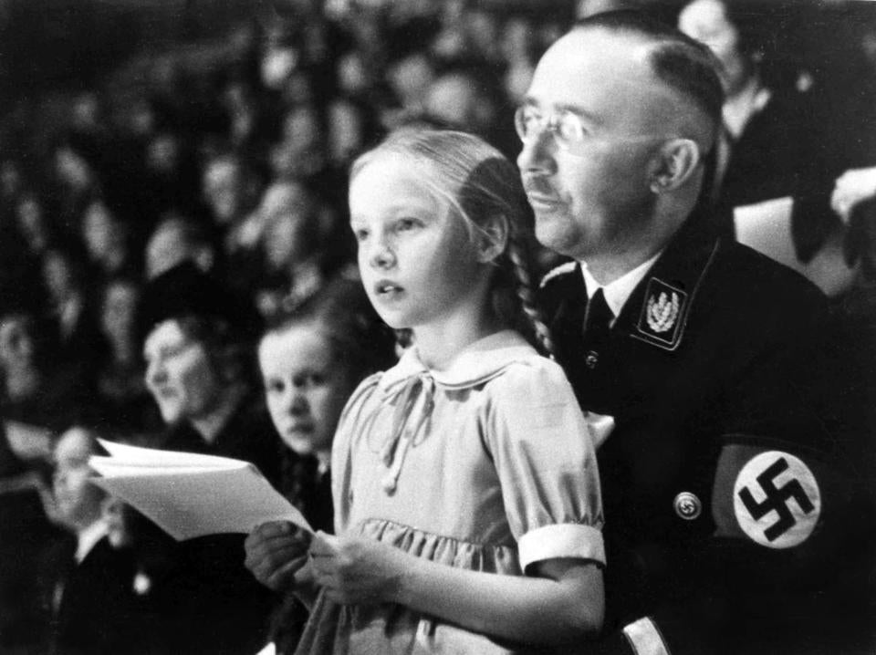 FILE - In this March 6, 1938 file photo Chief of the German Police and Minister of the Interior Heinrich Himmler, with his daughter Gudrun on his lap, watch an indoor sports display in Berlin. Germany's foreign intelligence agency is confirming that the daughter of top Nazi Heinrich Himmler, who led the SS, worked for it as a secretary in the early 1960s. The BND told Bild newspaper Friday that Gudrun Burwitz-Himmler, who herself was a notorious postwar supporter of the extreme right, served as a secretary from 1961 to 1963. (AP Photo)