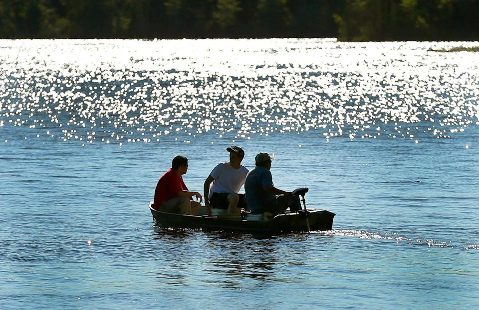 Men sat in a boat on West Lake of Monponsett Pond in Hanson. A kayaker was pulled out Saturday.