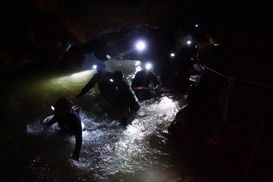A handout photo made available by the Royal Thai Navy on shows a Thai 'Navy Seal' Underwater Demolition Assault Unit team wading through the flood as they inspect inside the cave during a search and rescue operation for a missing football team at the Tham Luang cave in Tham Luang Khun Nam Nang Noon Forest Park in Chiang Rai province, Thailand, 30 June 2018.