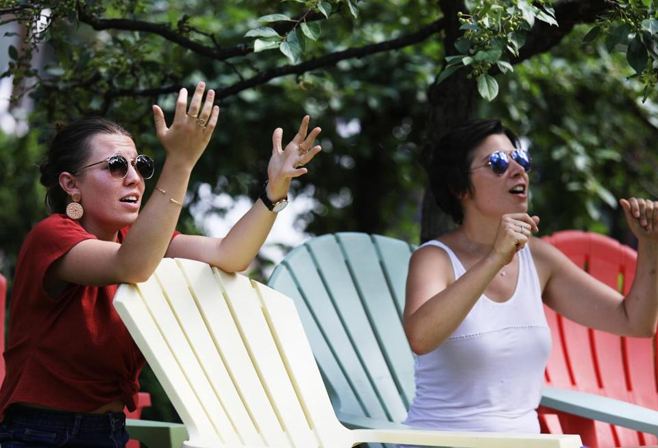CAMBRIDGE, MA - 07/10/2018 Sarah Terriere, left, and Lea Sasbortes, both visiting Boston from France, react to the Belgium and France World Cup game. A crowd of a few dozen people gathered to watch France play Belgium on a Jumbotron at University Park Commons. Erin Clark for the Boston Globe