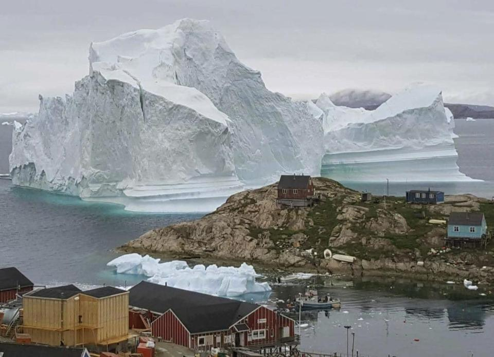 Huge iceberg drifts close to a village on Greenland's coast